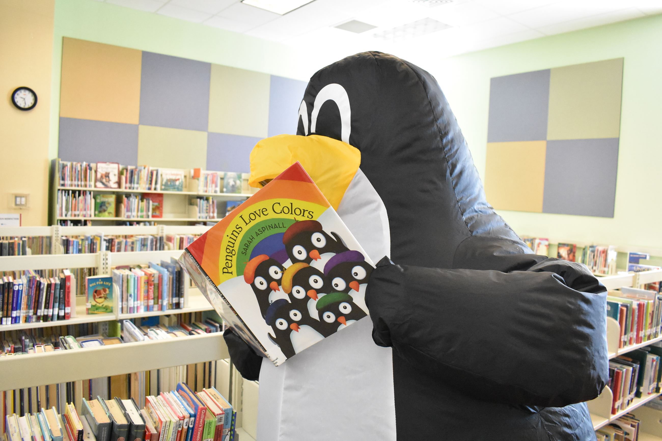 Inflatable Penguin Mascot Reading Kids Book in Library