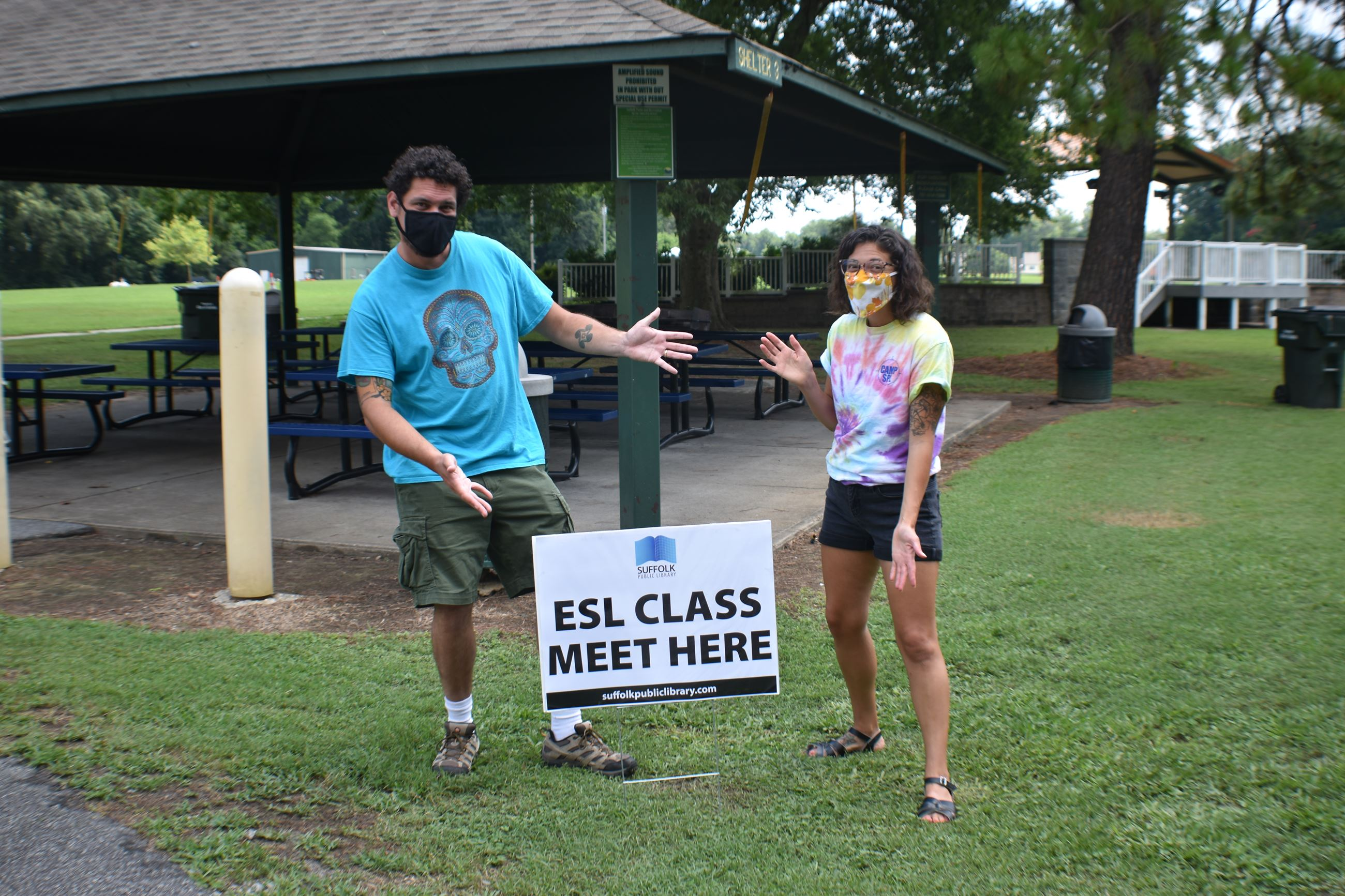man and woman wearing face masks at park in front of shelter pointing at sign that says esl class